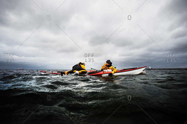 Friends in kayak helping each other