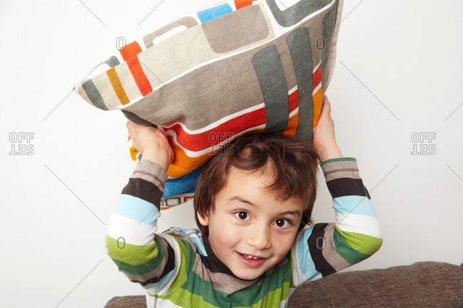 Boy throwing cushion