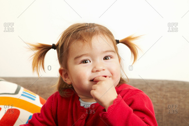 Young girl on sofa with fingers in mouth