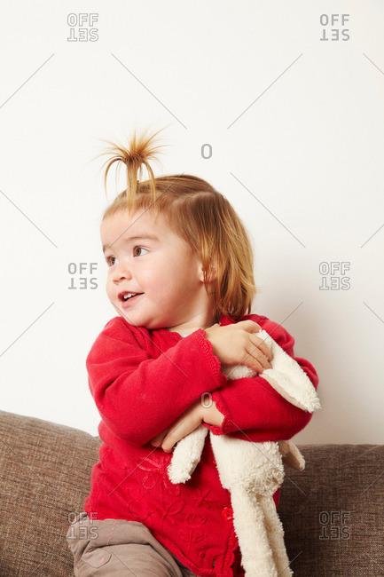 Young girl with teddy bear on sofa