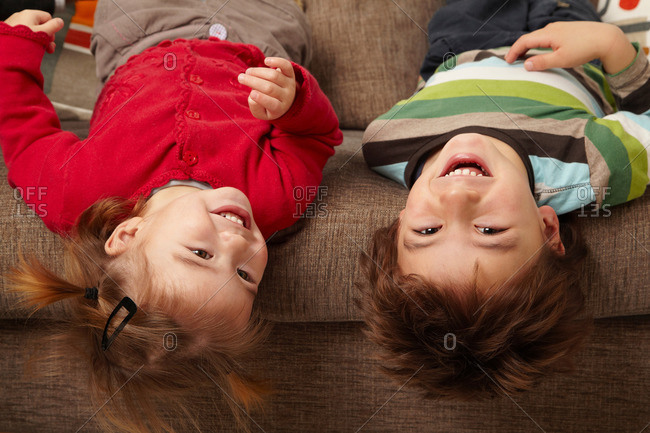 Young boy and girl laughing on sofa