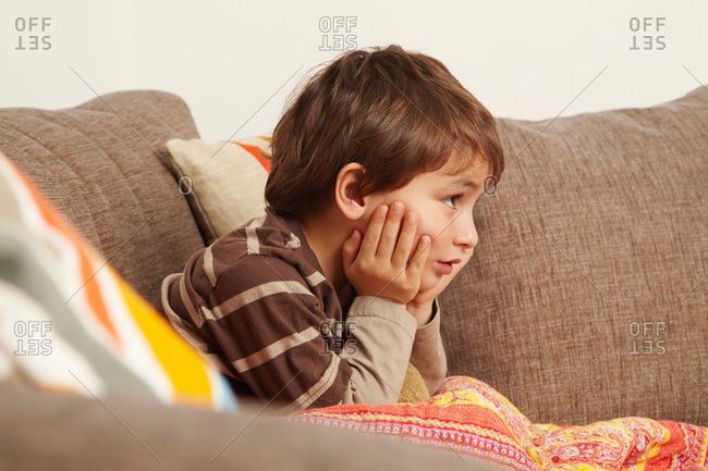 Boy on sofa staring at television