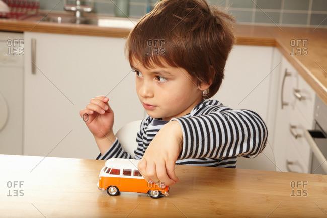 Boy pushing toy car on kitchen surface