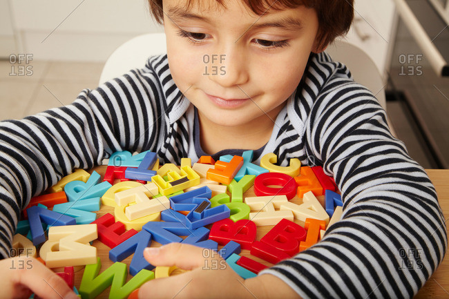 Boy playing with letters in kitchen