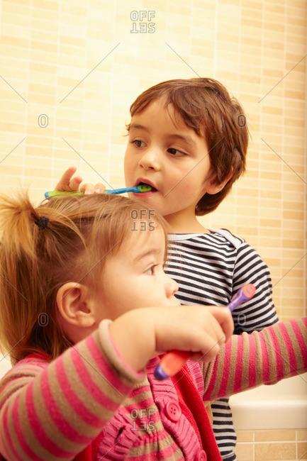 Boy and girl brushing teeth in bathroom