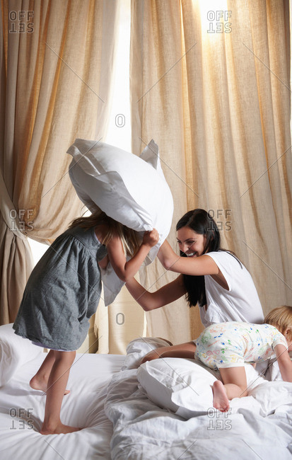 Pillow fight between mother and daughter