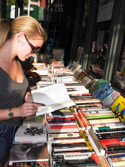 Woman reading a book, in a bookstore