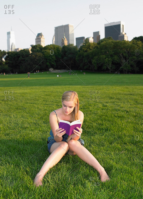 Woman reading a book in central park