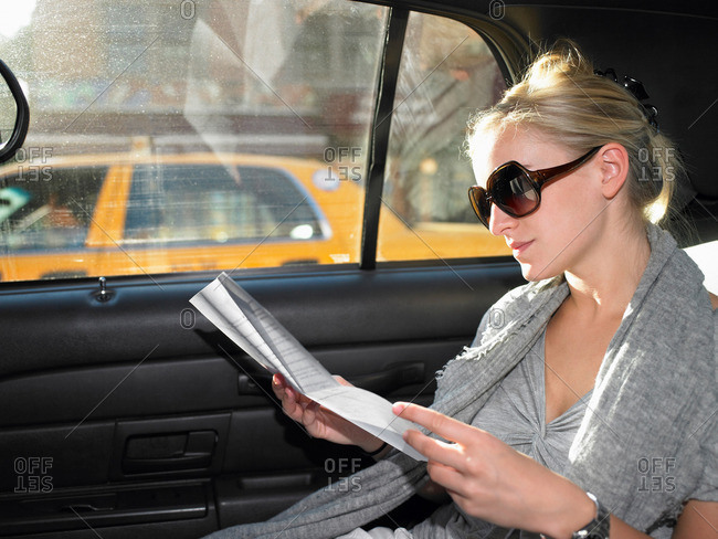Woman reading a letter in a taxi
