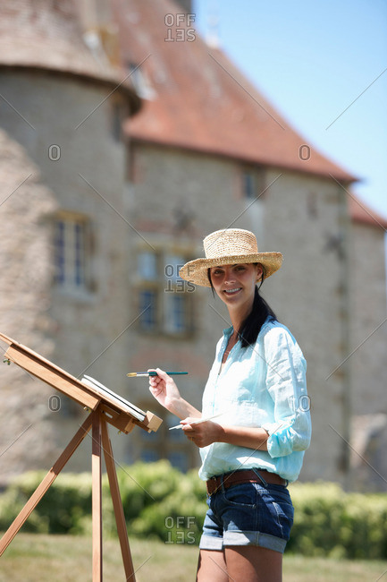 Woman painting a picture, outdoors