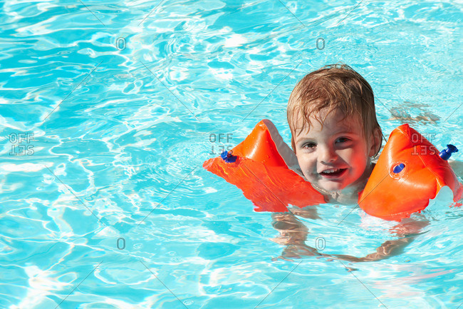 Baby boy swimming with water wings