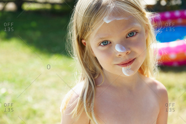 Girl with sunscreen cream on her face
