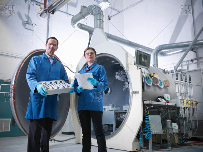 Male and female scientist with product looking to camera, stood in front of vacuum tank in engineering factory