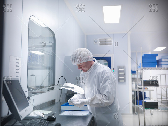 Male scientist working with product under lamp in clean room