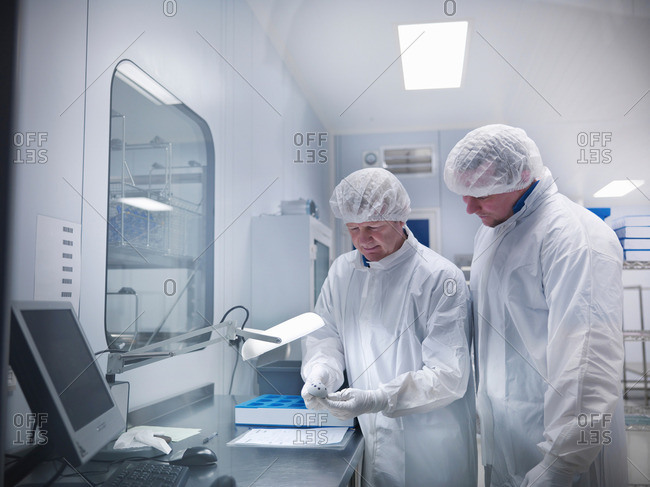 Male scientists working with product under lamp in clean room