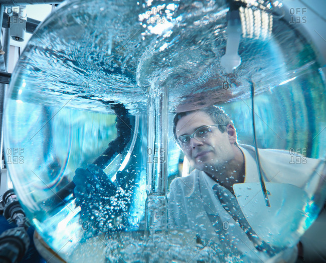 Scientist looking through mixing vessel