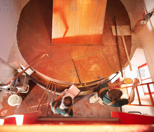 Workers with sample at copper tank