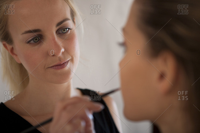 Makeup artist applying lipstick to model with lip brush