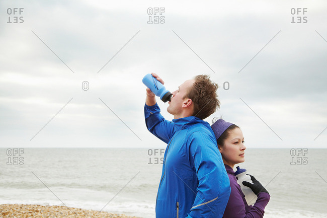 Couple recovering from exercise on beach