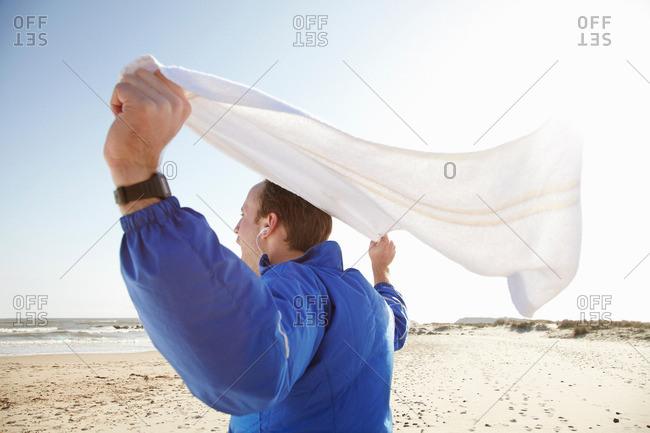 Sporty man celebrating at beach in sun