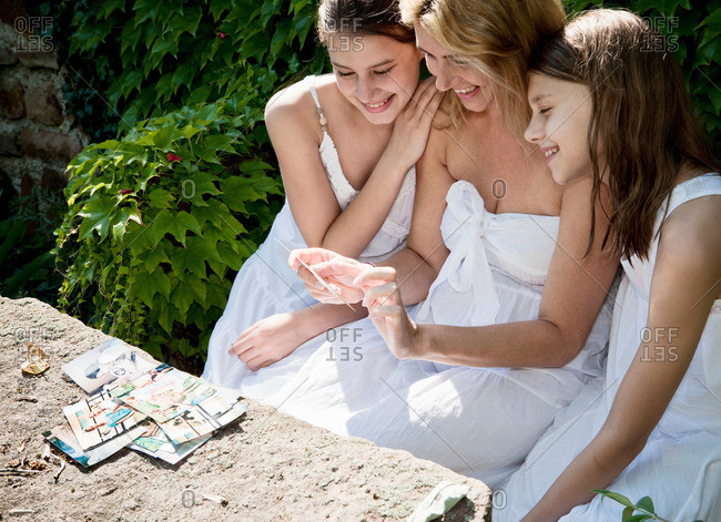 Mum and daughters looking at family pictures