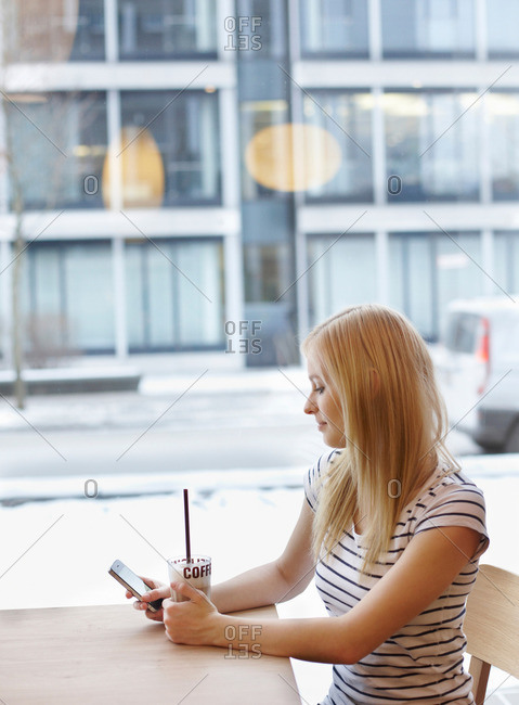 Woman with coffee and cellphone