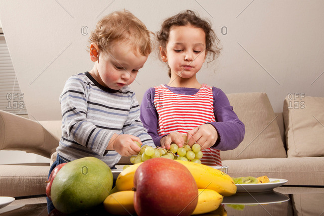 Boy and girl eating fruit