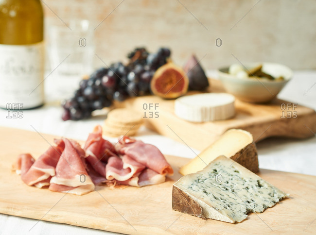 A cheeseboard with charcuterie, grapes and figs