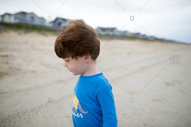 Young boy exploring beach with oceanfront homes