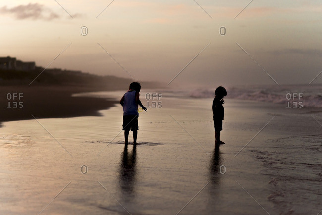 Boys standing on beach during high tide at sunset
