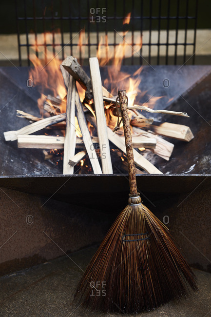 A broom propped against a small fire pit