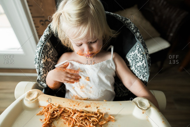 Girl sitting in a high chair eating a messy meal of spaghetti noodles and tomato sauce