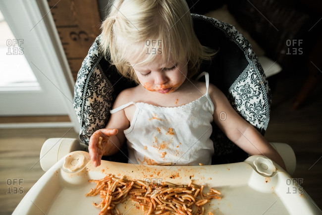 Girl sitting in a high chair eating a messy meal of spaghetti noodles