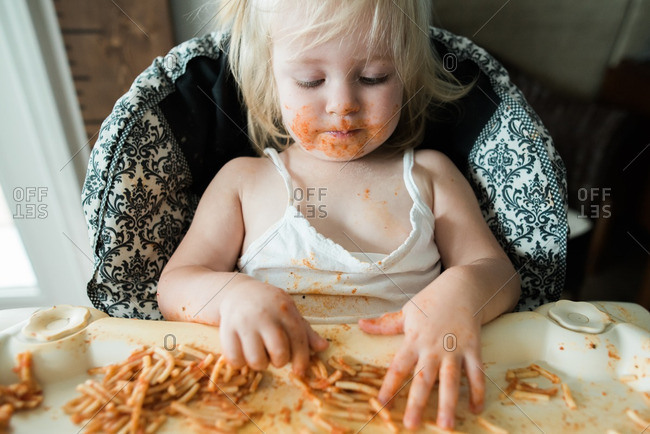 Girl sitting in a high chair eating a messy meal of spaghetti