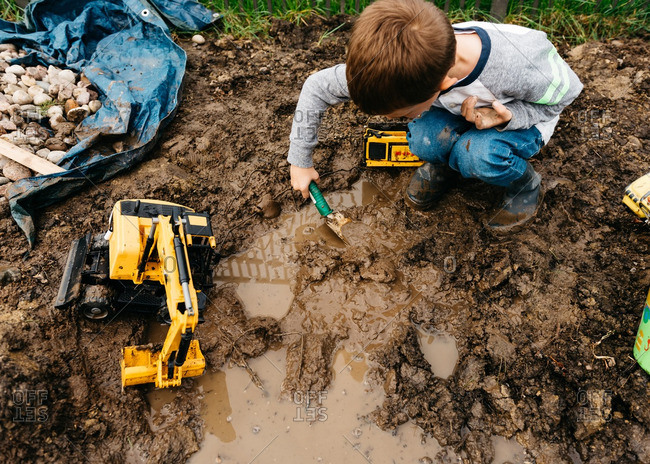 Boy playing by himself in the mud