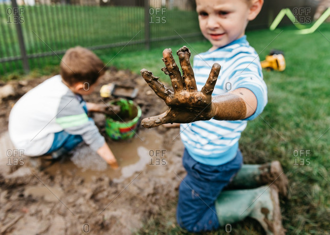 Two boys playing in the mud in their side yard