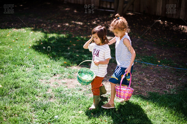 Boy and girl looking for eggs with Easter baskets in yard