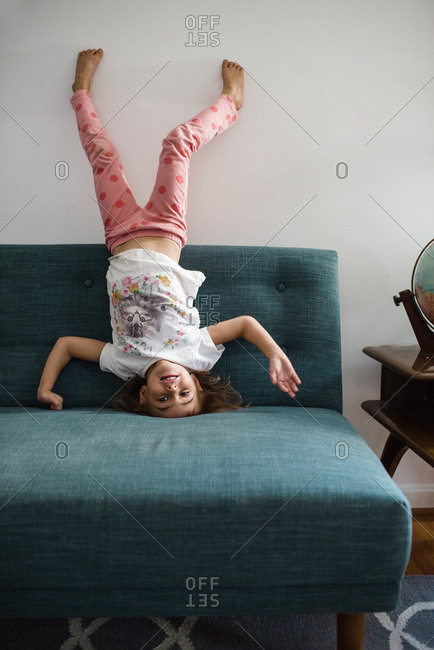 Little girl doing a headstand on a sofa