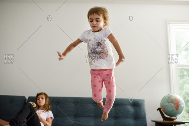 Little girl jumping off of a sofa
