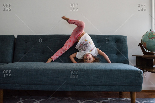 Little girl doing handstand on a sofa