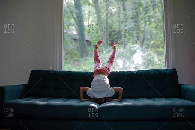 Little girl doing a headstand on a sofa in front of a window