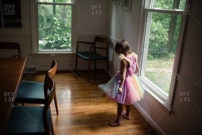 Little girl standing by a window in a colorful dress