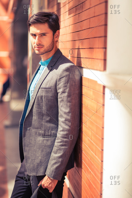 Portrait of stylish man leaning against building