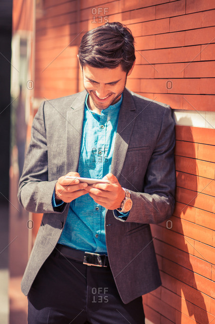 Man using smartphone while leaning against building