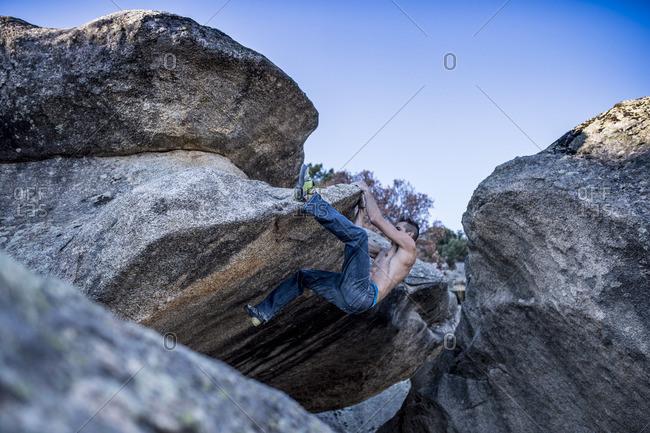 Man in jeans free climbing rocks