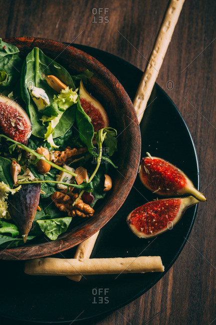 Spinach salad with cheese, figs, and nuts in wooden bowl