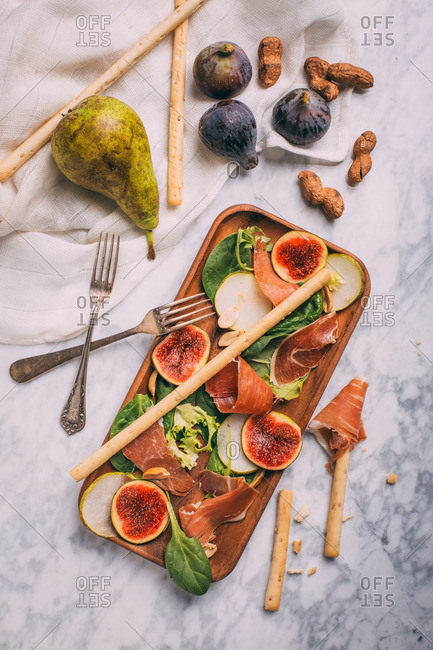 Salad with greens, sliced figs, pears, and prosciutto arranged with ingredients