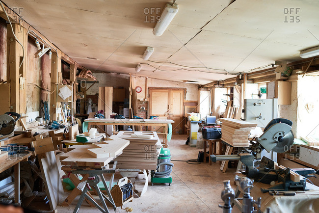 Carpenter's workshop full of various wooden pieces and planks on the tables and miter saws