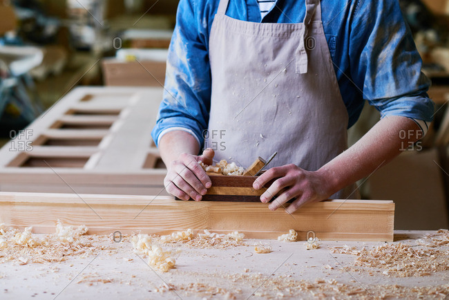 Close up of a craftsman using a wood plane in his workshop