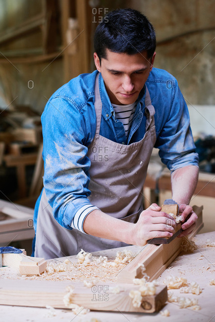 Craftsman using a shaving wood with a wood plane in his workshop